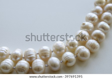 a pearl necklace on a light background