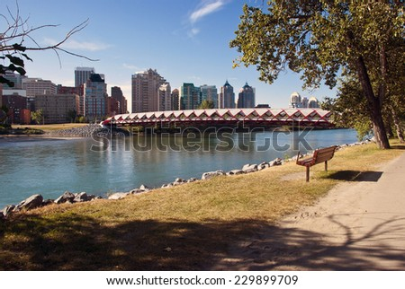 A pedestrian bridge across  Bow River in Calgary with skyscrapers in the background. - stock photo