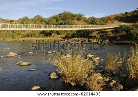A pedestrian bridge over flood prone river in KZN South Africa - stock photo
