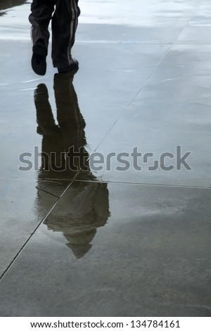 A pedestrian's reflection on the wet concrete pavement on an inclement and wet winter day.