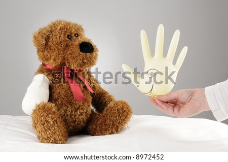 a pediatrician trying to cheer up an injured teddy bear a hospital balloon - stock photo