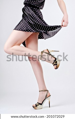 A peek of sexiness. Hot girl with mini skirt and sexy long legs in high heels. - stock photo