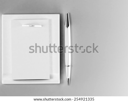 a pen and a paper on the gray background - stock photo