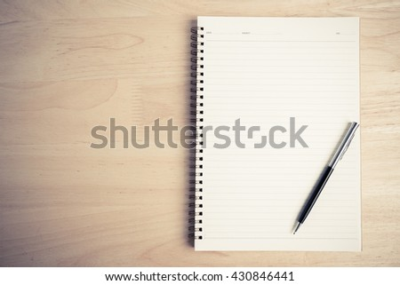 a pen and blank paper of open book on the table - stock photo