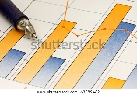 A pen composed over a business chart of earnings trends. - stock photo