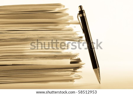 a pen near stack of paper - stock photo