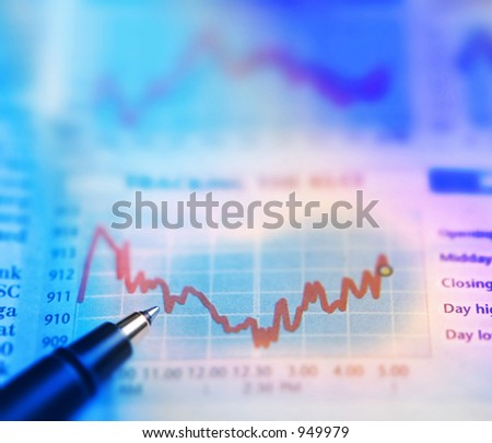 A pen on stocks chart of a newspaper - stock photo