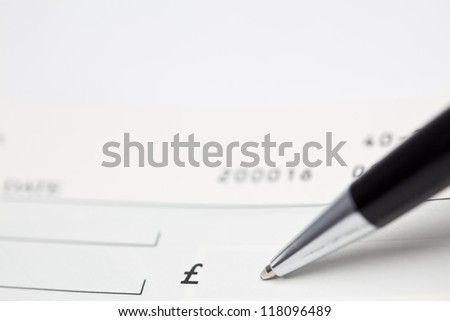 A pen ready to write a sum of Pounds on a cheque - stock photo