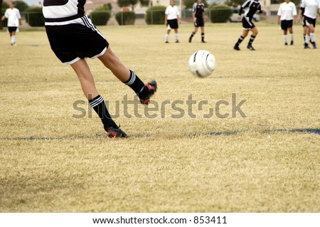 A penalty kick in a girl's league soccer game. - stock photo