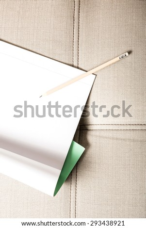 A pencil and a blank exercise book on a sofa.  - stock photo