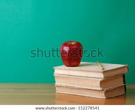A pencil and a red apple on a pile of books