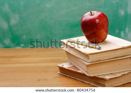 A pencil and a red apple on a pile of books - stock photo