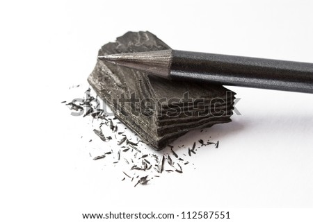 a pencil lying on a piece of coal in the shavings - stock photo
