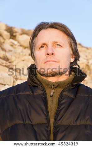 A pensive looking forties male with stubble looks out at the setting sun after a day spent walking in the mountains. - stock photo