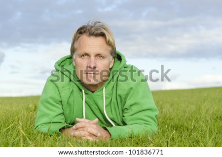 A pensive looking man laying on grass