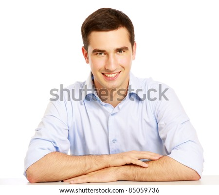 A pensive smiling man at the desk is looking up, isolated on white