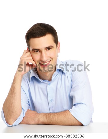 A pensive smiling man at the desk is looking up, isolated on white - stock photo
