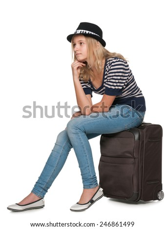 A pensive teen girl is sitting on a suitcase - stock photo