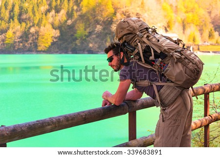 A pensive young  hiker with backpacker and sunglasses is leaning with his arms against a wooden railing, looking at a mountain lake - stock photo