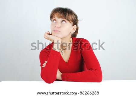 A pensive young woman in a red sweater at the desk, isolated on white - stock photo