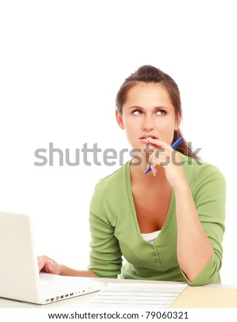 A pensive young woman in front of a laptop, isolated on white - stock photo