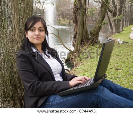 A pensive young woman with laptop computer, sitting by a small lake. - stock photo