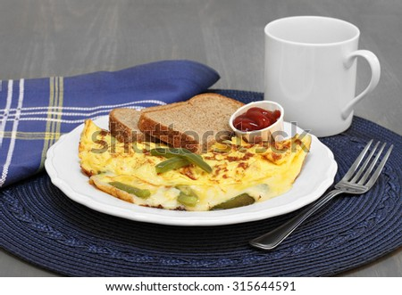 A pepper, egg and cheese omelet with a slide of healthy whole grain toast. - stock photo