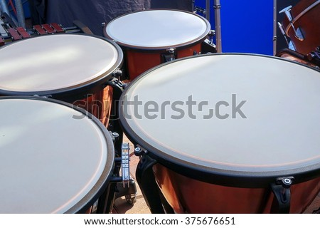 A percussion ensemble features large timpani drums