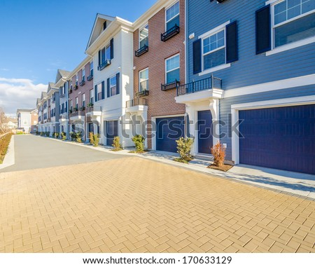 A perfect neighborhood. Apartment buildings (townhouses) in suburb at Spring in the north America - stock photo