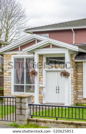 A perfect neighborhood. Houses in suburb at Fall in the north America. Fragment of a luxury house with entrance door and nice window.