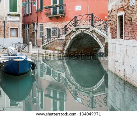 A perfect reflection of the bridge in the water of the old canal - Venice, Italy - stock photo