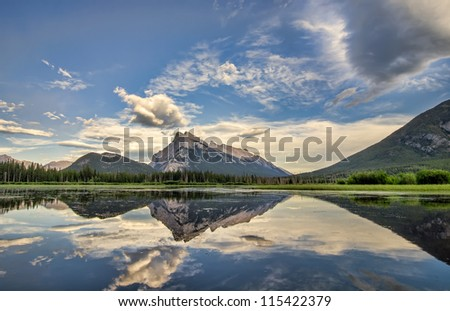 A perfect reflection of the rocky mountains in Vermilion lakes, in Banff National Park Canada. - stock photo