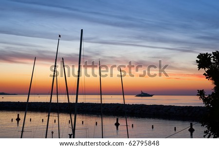 A perfect sunrise, with boat masts and a yacht