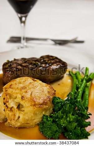 A perfectly grilled steak served with broccolini and a potato cake with gravy and red wine. - stock photo