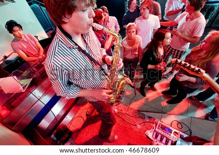 A performance of a saxophonist and guitarist in a nightclub with DJ. - stock photo