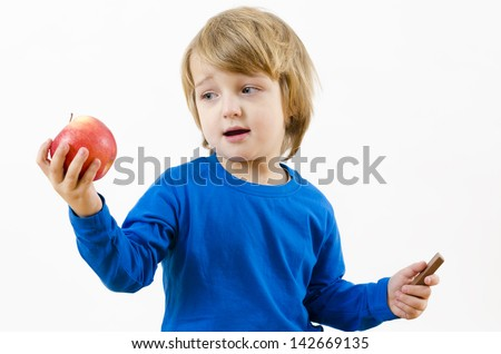 A perplexed blond boy fighting with food temptation - stock photo