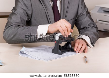 A person at a desk using a stamp on documents - stock photo
