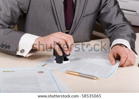 A person at a desk using a stamp or corporate seal on documents - stock photo
