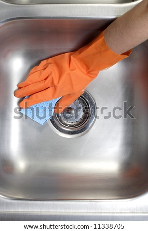 A person cleaning the kitchen sink with a glove - stock photo