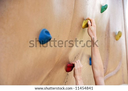 A person climbing a rock wall in the park - stock photo