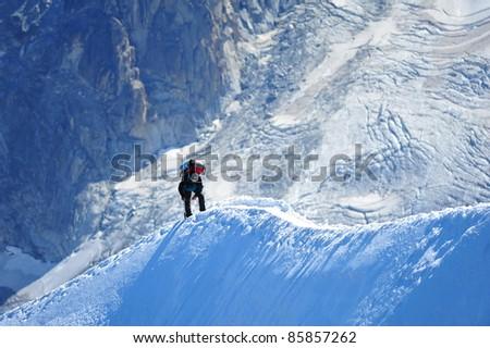 A person climbing along the mountain ridge near Monte Blanc - stock photo