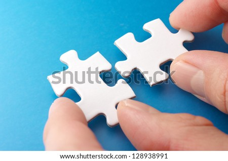 A person connecting puzzle pieces.Concept image of building. - stock photo