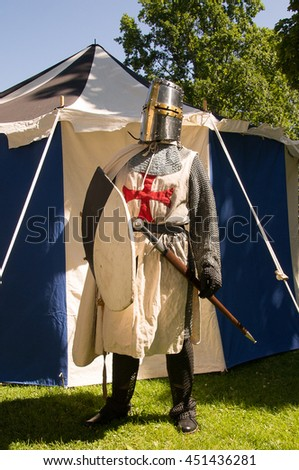 A person dresses up historically to mimic a knights templar in full armour  standing in front of a white and blue tent holding a shield. - stock photo