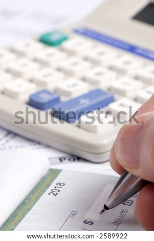 A person fills out a check... paying the bills. - stock photo