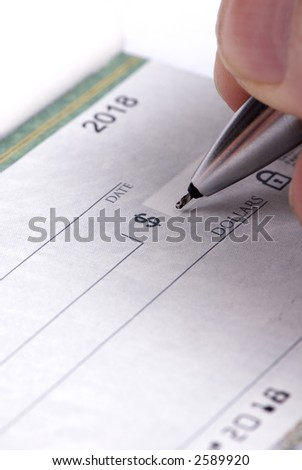 A person fills out a checkbook ...paying the bills - stock photo