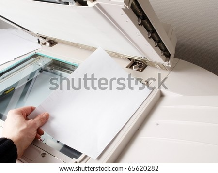 A person handling a multi purpose copier machine - stock photo