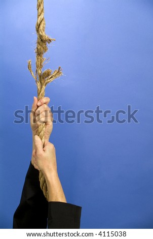 A person hanging on to a rope that is frayed and about to break. - stock photo