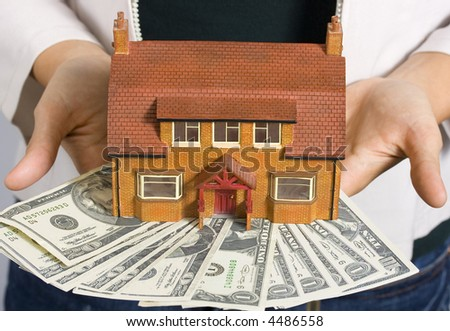 A person holding a miniature house and some dollar bills - stock photo