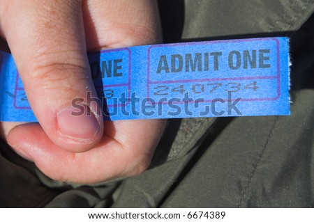 A person holding a string of admission tickets. - stock photo