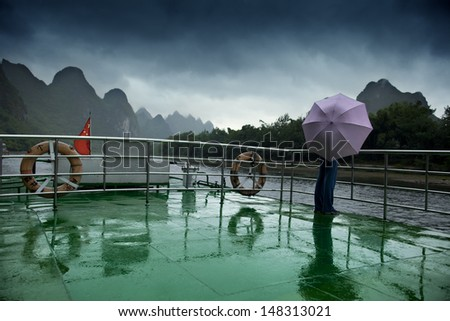 A person holding an umbrella on a boat deck during Li river cruise, in China, on a cloudy day. - stock photo